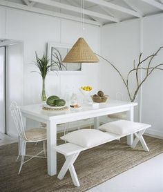 An all-white colour scheme keeps things chic. To create an eclectic yet cohesive dining set, the cottage owner paired metal bistro chairs found at a flea market with an affordable picnic bench, and then painted everything out.