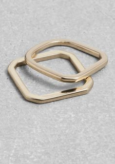 A pair of square-wire rings with two different angular shapes that give your finger a geometric spin.