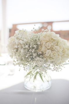 Simple and elegant wedding centerpiece: white hydrangea with babies breath in a clear vase.