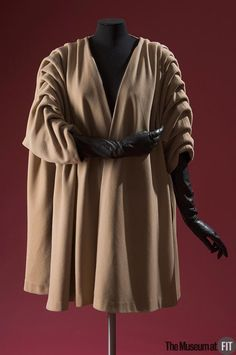 Coat (front view) | Cristóbal Balenciaga (Spanish, 1895-1972) | France, Fall 1950 | Beige wool duvetyn | The simplicity of Balenciaga's most innovative designs is perfectly realized in this garment. The visible folds are formed and anchored to a ribbon that runs inside the upper part of each sleeve, from the neckline to cuff, and the folds are tacked to the ribbon at approximately four inch intervals | The Museum at FIT