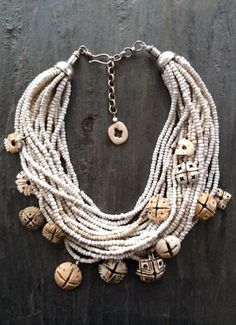by Anna Holland | Antique carved conus shells from the deserts of Mauritania, once used as currency by tribes in Africa as early as the 14th century. With twenty strands of old white glass beads from Africa. Sterling silver cones and a hook and eye clasp | 825$ by lilia