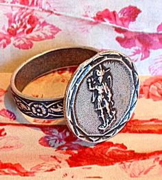 """Vintage Saint Michael the Archangel Ring, Silver Oxidized metal, floral band has hidden adjustment under the top. The ring is size 6.5 as is and may be adjusted up a few sizes.  5/8"""" in diameter."""