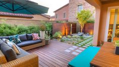 Clean, horizontal lines and inviting modern furniture characterize this zen patio and garden space. A lighted accent wall draws attention to the water feature, which is nestled into a rock garden with neat rows of succulents. Colorful cushions and pillows brighten the space and give the seating and dining areas a cheerful vibe.