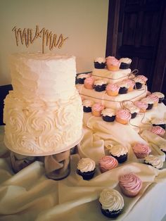 """Cake accompanied with cupcakes at the """"Love is Sweet"""" table"""