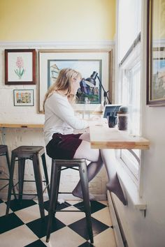 """I realized pretty early on, with limited floor space, I'd have to move up on the walls. And because it is a rented space, any changes I made had to be temporary. My pictures turned into magnets on the fridge. My pots and pans went into the air. I didn't have room for a kitchen table, so I built a wrap around coffee bar for the walls (inspired by Emma's standing desk, actually!). I have hanging mason jars in the bathroom and wire file storage hanging by my desk. To make the room look bigger…"
