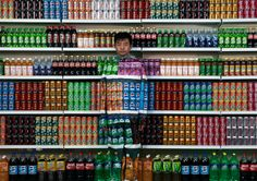 """Chinese artist Liu Bolin waits for his colleagues to put a finishing touch on him to blend into rows of soft drinks in his artwork entitled """"Plasticizer"""" to express his speechlessness at use of plasticizer in food additives, in his studio at the 798 Art District in Beijing, China, on August 10, 2011. (AP Photo)"""