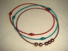 ($0.75) Sold in set of 3! Vibrant and colorful stretch coil bracelets are super lightweight and slinky and feel great on! Matching round beads add easy style to these bracelets. Wear all at once or mix with other fun colors. Colors include teal green, red, and dusty rose! stretch brass and acrylic 2.5mm and 4mm rounds 7-inches