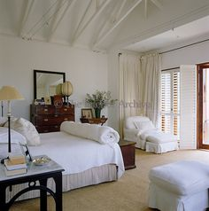 This bedroom has been decorated in shades of white, stone and black and has plantation shutters that lead on to a small balcony with a view ...