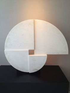 White veined marble sculpture on black metallic stand by Angelo Mangiarotti.