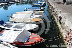 Multiple covered small sea boats docked with at least two sailor ropes in a row at local sea canal in Rijeka, Croatia.