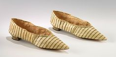 Striped leather slippers by J. Staton, British, 1795-1810. Colored and patterned shoes and coordinated accessories were often worn as counterpoint to the white cotton dresses of the neoclassical period. An appealing striped pattern and color scheme enliven this pair of slippers, which feature the sharply pointed toe and low heel then in fashion. The high quality is displayed in the beautifully finished soles, which are burnished to form a decorative design accentuating the angular shape.