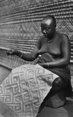 A women hand-embroiders traditional kuba cloth in the DOC.