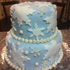Idea for Luke Cake. This one requires the same standard frosting tip for the small snowflakes and balls as described in the pink cake pin. However, this cake involves blue fondant (smooth frosting) and white fondant pre-cut into snowflake shapes