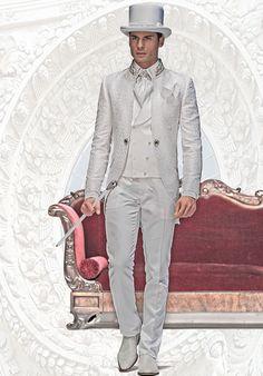 Bräutigam Anzug, Redingote mit Posamenten-Stehkragen, weiß, aus Brokat-Stoffen, koordiniert mit Hose und Weste, zweireihig geknöpft, weiß, aus Taft, weißes Hemd mit Silber-Stickerei, Ascot mit Einstecktuch farblich abgestimmt, Nadel mit Edelkristall, Zylinder, weiß, aus Taft mit Edelkristall, weißer Stock mit Silber-Griff und weiße Schuhe.