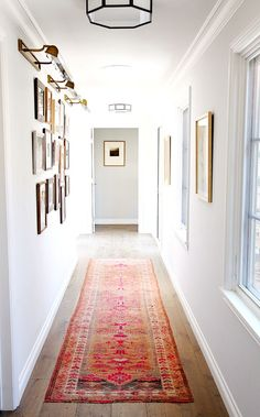 Hallway with white walls, framed artwork, wood floors, and bright patterned rug: