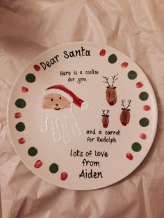 Christmas Santa plate. Each reindeer is a thumbprint (dad, mums and son) And the santa is my sons hand print. Merry Christmas Santa!!