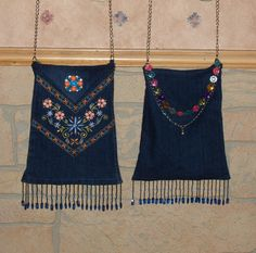 2 jean purses made from the (already embroidered) legs of a pair of little girls jeans, lined w/fabric & decorated w/beaded fringe & a decorative pin.  The handle is a jeweled belt from Claire's.  The chain portion is used for the actual handle w/the beaded portion draped in the back for decoration.  I made the back piece triangular @ the top so that it would fold down over the top.  The pin weighs the flap down to keep it folded over.  I made these for gifts for 2 of my great-nieces.