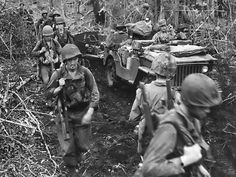 Men of the US First Marines Division at Cape Gloucester, New Britain, Bismarck Archipelago, circa late Dec 1943; note jeep being used to haul supplies.