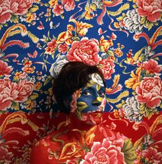 """In her """"Landscape Series,"""" Peruvian artist Cecilia Paredes uses body paint, makeup and other materials to blend into colorful wallpaper backgrounds."""