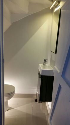 Small modern understairs powder room works because the bathroom furniture is kept to scale.