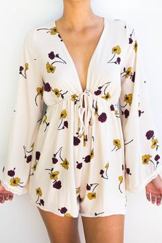 Vintage inspired floral romper feature deep v neckline with tie at the front and lace lined bell sleeves. This romper is also available in black.