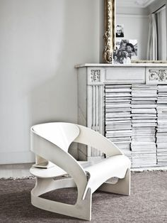 Mantelpiece in home designed by Vincent van Duysen. Nice way to store magazines!
