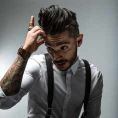 Slick hair, tatted arm, suspenders, fitted collar short and scruffy beard
