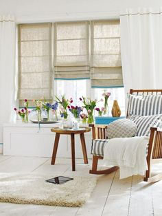 love the tan drapes + colorful flowers on window sill