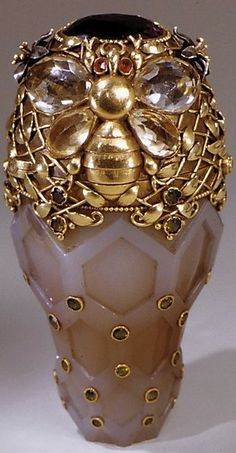 Designed by Paulding Farnham (1859–1927) For Tiffany and Co.: ca. 1893 Gold, agate, yellow sapphires, dementoid garnets, red garnets, and amethyst.Honey is the thematic scheme of this unique vessel. The agate body suggests the cell-like shape and waxen material of the honeycomb; the diagonal pattern, its texture. The lid's surface features honeysuckle leaves, honeybees, and bumblebees. This small object was one of the jewels of the Tiffany & Company display at the Chicago Exposition of 1893