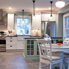 White kitchen, teal island, love the place for cookbooks.