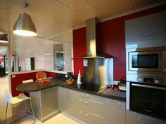 Cuisine moderne avec mur peint en rouge et verrière intérieur. On aperçoit un plan de travail gris d'angle placé sur une meuble de rangement de cuisine de couleur blanche. Le reste du mobilier de cuisine est argenté.