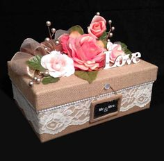 "Wrap up gifts for someone special in this tastefully decorated burlap covered box. A delicate string of pearl beads lines the ivory lace all around the sides. The wooden word ""love"" is accented with rhinestones and glued to the top. 