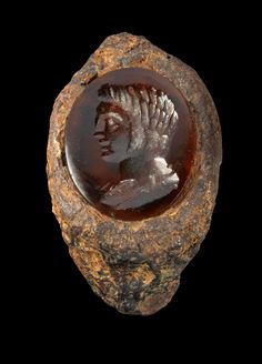 Iron ring with a gemstone of red glass showing a male bust. Roman, 2nd - 3rd century A.D. Ring corroded.