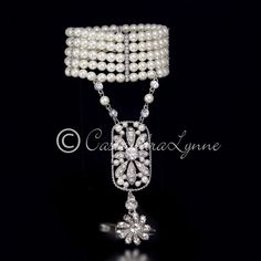 This wedding hand-chain is styled after The Great Gatsby piece worn in the movie. Five rows of ivory pearls are accented by rhinestone dividers and stretch to fit most wrists. The chain is adorned wit