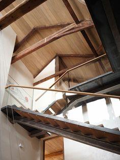 Das Treppenhaus ist bis unters Dach geöffnet und verbindet drei Stockwerke mit einer luftig wirkenden Stahl-Glas-Holz-Konstruktion.