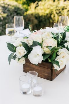 light and airy floral centrepieces with pastel blooms and lots of greenery in rustic wooden box vases with clustered candles | Rustic Fall Ranch Wedding in Santa Ynez