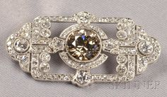 Art Deco Platinum, Colored Diamond and Diamond Pendant/Brooch, centering a fancy colored transitional-cut diamond weighing approx. 3.77 cts., further set with old European and old single-cut diamonds, approx. total wt. 7.17 cts., millegrain accents, lg. 1 3/4 in.