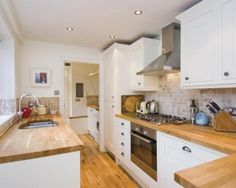 white kitchen, oak worktop and floor and beige wall tiles. very nice.