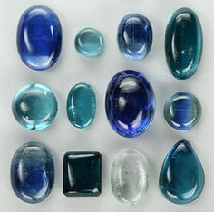 "Kyanite is often cut ""en cabochon"" or as a faceted gemstone. Shown above are kyanite cabochons ranging in color from clear, to blue to green and black."