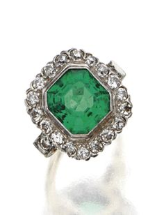 EMERALD AND DIAMOND RING, CIRCA 1930. The square emerald-cut emerald weighing approximately 5.30 carats, framed by 20 old European-cut diamonds weighing approximately 1.40 carats, mounted in 14 karat gold and platinum