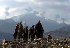Afghan War December 16, 2001: Anti-Taliban Afghan fighters watch several explosions from US bombings in the Tora Bora mountains in Afghanistan