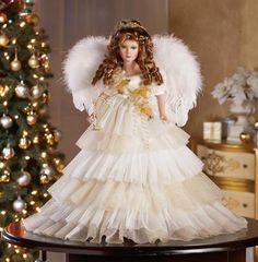 "This elegant angel from our Heritage Collection is special enough to display all year. She's dressed in tiers of netting in white and cream and wears feathered wings with a sprinkling of glitter. She holds a golden harp. Porcelain hands, feet & face. For decoration only – not a toy. Polyester. 18"" tall. - See more at: http://www.collectionsetc.com/Product/white-and-cream-shimmering-angel-collectible-doll.aspx/_/N-3axb#sthash.sU1M3jNA.dpuf"
