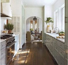 white kitchen with lovely floors looks great with an archway opening going into the dinning room.