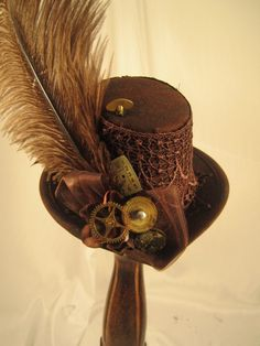 "Steampunk Brown Mini Tophat with Clock parts. New SteamPunk Brown Mini tophat with brown lace, measures about 6"" across and up and down, gears, clock parts brown feather and ribbon bow on the back."