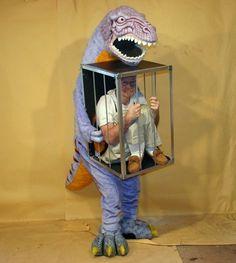 dinosaurio cargando en una jaula a un humano