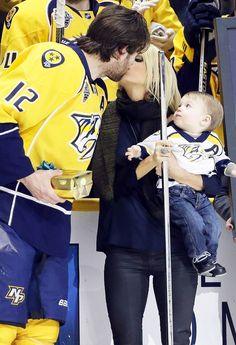 Carrie Underwood kissed husband Mike Fisher rinkside while their baby Isaiah looked on — see the adorable pic!