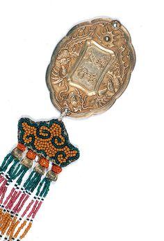 KIM BÔI DE PREMIÈRE CLASSE en argent doré, de forme ovale, le contour lobé, à décor des quatre caractères chinois Quýnh Dieu Vinh Háo logés dans un encadrement polylobé ceinturé de phénix parmi les nuées et perle enflammée, le revers assorti orné d'un Niên Tao en quatre caractères. Passementerie de perles multicolores à chauve-souris et pendeloques. Vietnam, Royaume d'Annam, début du XXe siècle. Haut. 7 cm - Poids (brut) 39 g./H. 2 3/4 in. - W. (gross) 0.078 lb