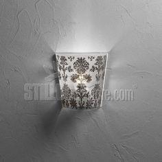 Emporium Babette Parete Paralume conico in policarbonato antiriflesso, decorato con texture nei colori bianco, nero, oro e argento.  Supporto in  metallo verniciato bianco.