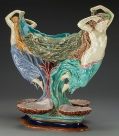 A French Majolica Figural Centerpiece, 19th century. The seaweed textured, lozenge-form bowl supported by flanking swimming maidens with diaphanous covering forming the standard above four shell-form dishes, all raised on a stepped diamond foot.