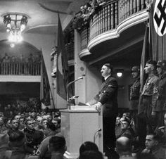 "1939: Adolf Hitler addresses the party faithful at the Munich Beer Hall which was at the center of his abortive attempt to take over by force of arms in 1923. Right behind him stands  SS Sturmbannführer Jakob Grimminger carrying the ""Blutfahne"", the Blood Flag of the Nazi party used on Nov 9, 1923 and supposedly stained with the blood of fallen comrades."